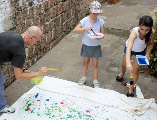 O artista Ney Caminha desenvolvendo trabalho no local com as ajudantes Laura e Ana.